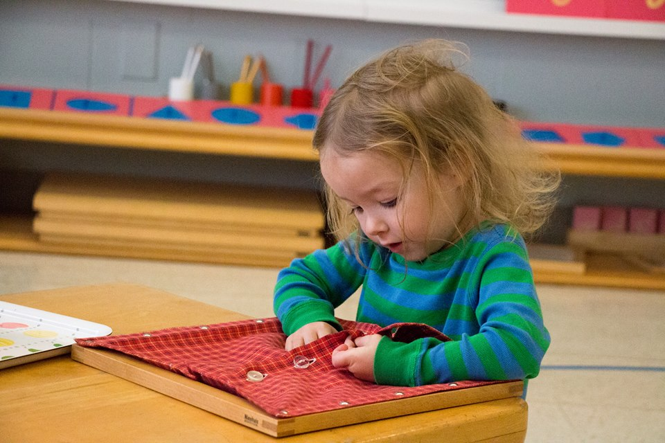 An Aidan Primary child concentrates on her work with a dressing frame